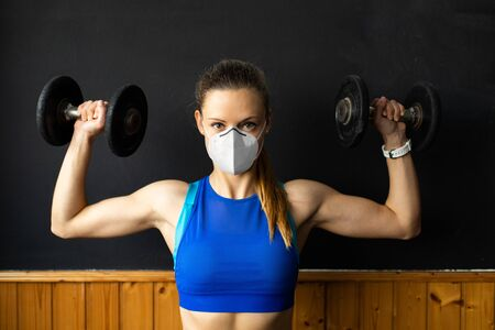 Young fit woman with n96 face mask doing shoulder press exercise at the gym with dumbbells.