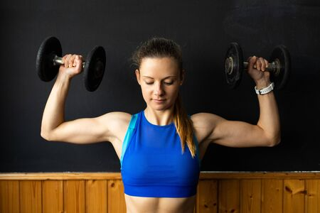 Young fit woman doing shoulder press exersice at the gym with dumbbells. Fitness strength workout.