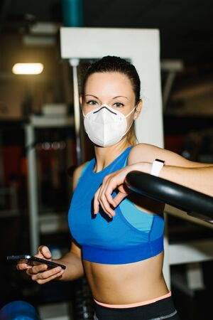 Young fitness woman working out in the gym wearing n95 face mask for protecting against Covid-19 infection.