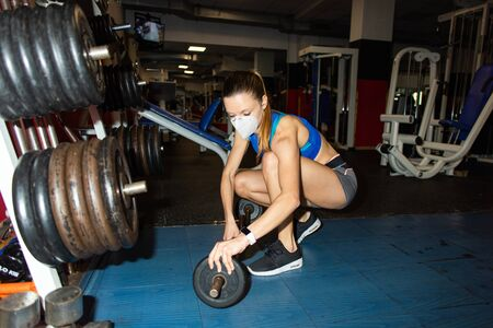 Young woman with n95 face mask adding weights to the bar during gym fitness workout under coronavirus Covid-19 crisis.