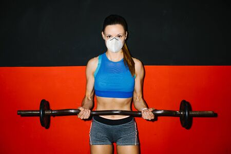Young fitness woman wearing n95 face mask working out arms biceps in the gym under coronavirus Covid-19 health crisis. Stockfoto
