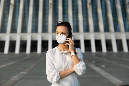 Young professional woman on cellphone business call outside under coronavirus Covid-19 health crisis. Business woman wearing facial mask for avoid infection.