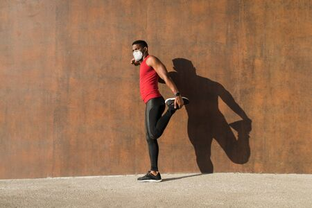 Urban athlete stretching and exercising wearing n95 face mask for protecting against Covid-19.