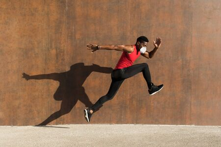 Powerful athlete training with n95 face mask for protecting against Covid-19. Young black man running and jumping casting shadow on a wall.