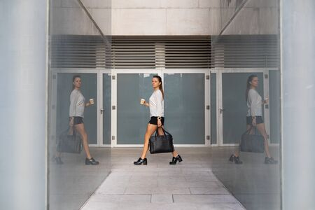 Young professional woman going to work carrying a coffee cup.