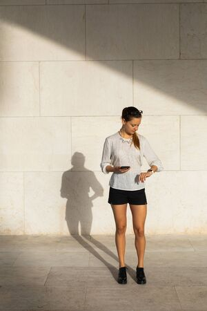 Young stylish professional woman on her coffee break checking time and using her phone.