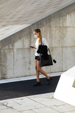 Businesswoman wearing n95 face mask for protecting against coronavirus. Young stylish professional woman walking on the street and texting on smartphone. Stockfoto