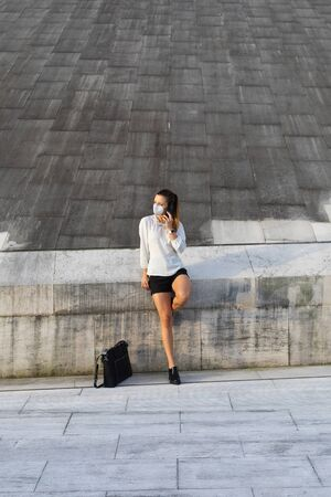 Businesswoman wearing n95 face mask for protecting against coronavirus. Young stylish professional woman taking a break outside for a cellphone call. Stockfoto