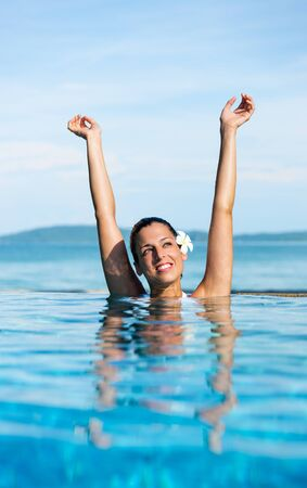 Beautiful happy woman relaxing in resort swimmming pool. Summer relax and vacation concept.