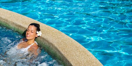 Beautiful tanned woman relaxing in resort pool spa. Relaxing outdoor jacuzzi. Stockfoto