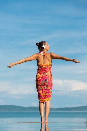 Back view of woman in thai summer dress looking the sea at Krabi, Thailand. Asia travel and relaaxing vacation concept.