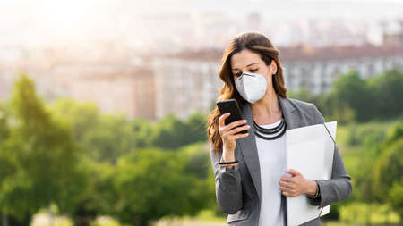 Young businesswoman wearing face mask outside during Covid-19 coronavirus health crisis. Professional woman using her smartphone. Stockfoto