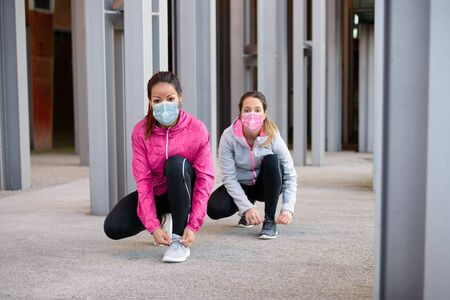 Sporty women wearing face mask and getting ready for urban running ot fitness workout under Covid-19 health crisis keeping social distancing.