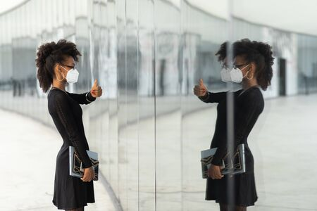 Successful stylish businesswoman with n95 face mask doing thumbs up gesture to herserlf in glass reflection. Professional black woman giving luck to herself under coronavirus Covid.19 health crisis.