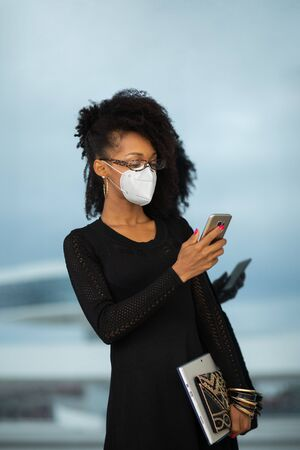 Young stylish businesswoman with face mask texting on smartphone. Professional fashionable woman outside using her phone under coronavirus Covid-19 health crisis.