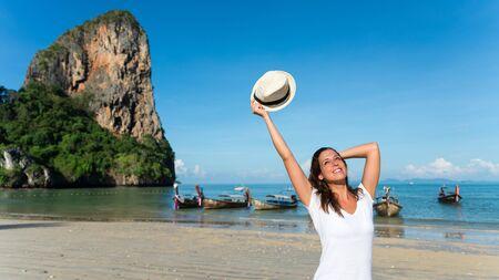 Happy woman enjoying travel vacation to Krabi, Thailand. Joyful brunette having fun and smiling on Railay Beach.