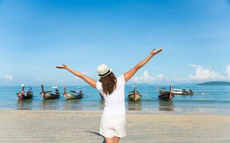 Woman enjoying freedom and having fun at Krabi, Thailand. Rear view of female raising arms towards the sea at Railay Beach.