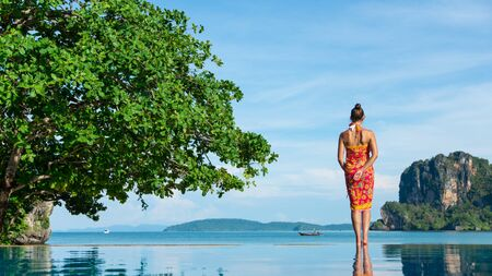 Back view of woman in thai summer dress looking the sea at Krabi, Thailand. Asia travel and vacation concept.