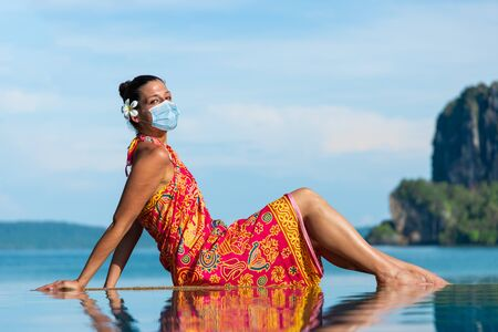 Woman in traditional thai summer dress wearing face mask for protecting against Covid-19 during vacation in Krabi, Thailand.