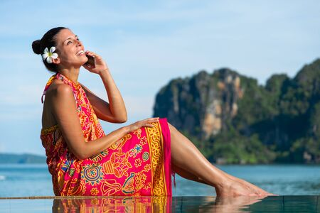Woman in traditional thai summer dress doing a phone call and relaxing in Krabi, Thailand.
