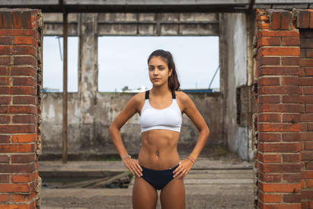 Motivated young female athlete taking a break during outdoor running workout at abandoned industrial ruins. Stockfoto
