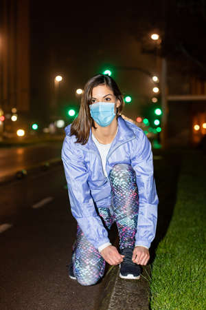 Young woman getting ready for urban night fitness and running workout wearing face mask against Covid-19. Gijon, Asturias, Spain. Stockfoto