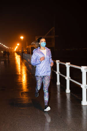 Sporty young woman runnning at night in the city wearing face mask against Covid-19. Gijon, Asturias, Spain.