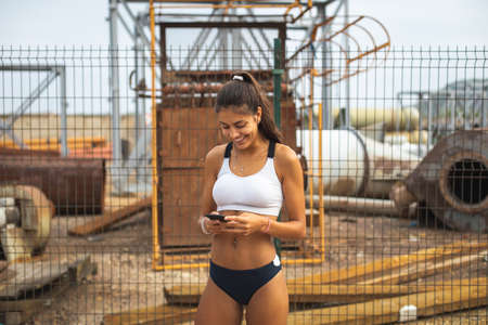 Fit slim young female athlete taking a workout rest for using running app on her phone. Outdoor urban training at industrial zone. Stockfoto