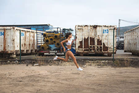 Fit slim young female athlete running at industrial zone. Sporty woman training.