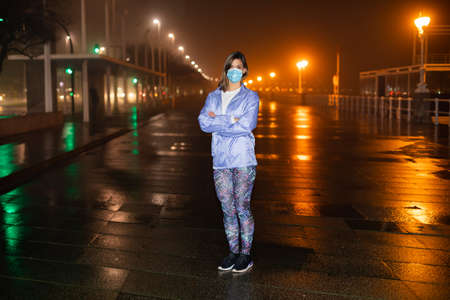 Condifent female athlete on urban night fitness and running workout wearing face mask against Covid-19. Gijon, Asturias, Spain.