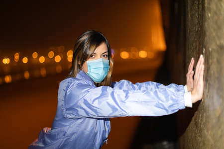Sporty young woman on city night workout wearing face mask against Covid-19.