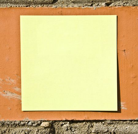 posting: Yellow Note On The Brick Wall Stock Photo