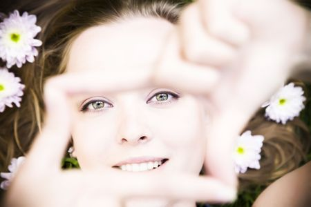 creates: Portrait of young woman creates a frame with her hands on nature background. Stock Photo