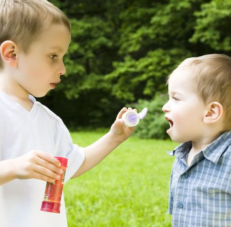 Two Boys Playing With Soap Bubbles photo