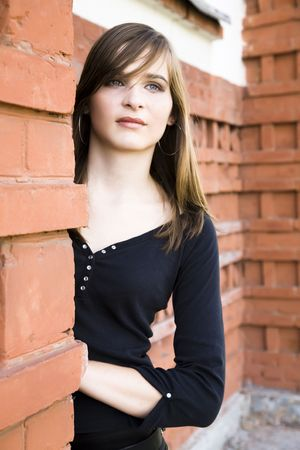 Beautiful Teenager Lady Against Red Brick Wall photo