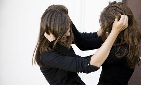 girl fighting: Conflict. Two Teenager Girls Fighting Outdoors. Stock Photo