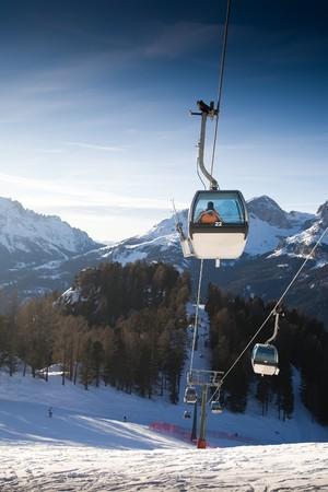 Ski lift cabins against clear blue sky. Italian Alps Resort. photo