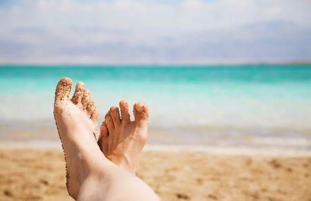 Female Feet On The Dead Sea Background photo