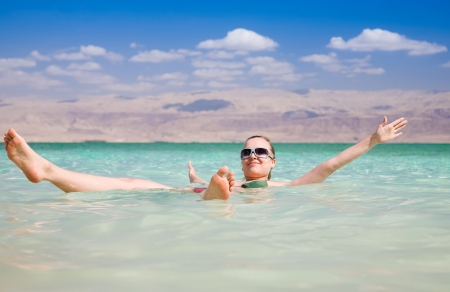 Beauty Woman Lying On Water. Dead Sea. Israel photo