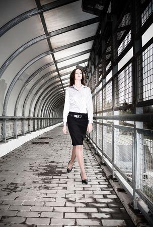Beautiful Businesswoman Walking On The Pedestrian Bridge. photo