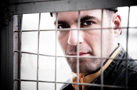 waiting convict: Man Close - Up Portrait. Behind An Iron Lattice Stock Photo