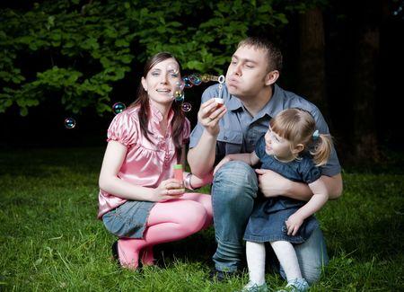 Father Blowing Soap Bubbles. Happy Family Portrait photo