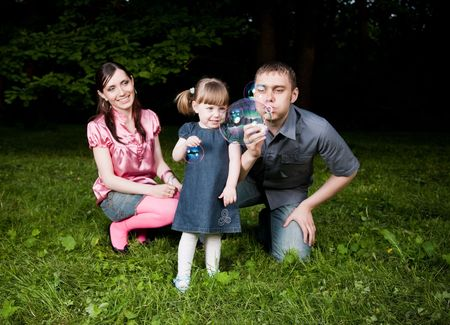 Big Soap Bubble. Family Playing On The Green Grass photo