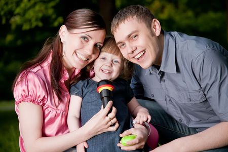 Family Lifestyle Portrait Of A Mum And Dad With Their Kid Having Fun Outdoors photo
