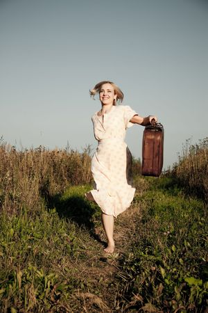 Young happy woman with a suitcase running on a rural road. photo