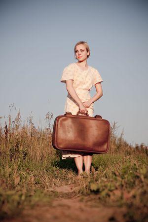 mujer con maleta: Mujer de pie con una maleta en un camino rural