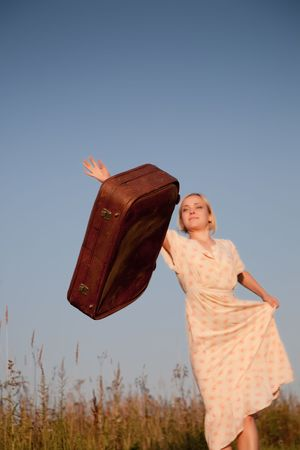 Young  beautiful woman throws a suitcase outdoors photo