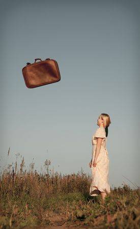 Beautiful woman looks at the falling suitcase photo