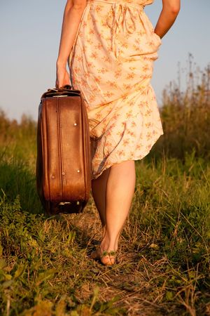 away: Woman with a suitcase takes on a rural road