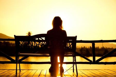 persona sentada: Mujer sentada en el banquillo en la puesta de sol